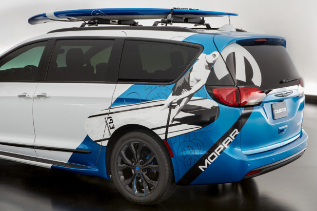 Custom Mopar graphics are wrapped on the quarter panel and rear of the white exterior of the Chrysler Pacifica Cadence, expressing the vehicle's active lifestyle, paddle boarding theme